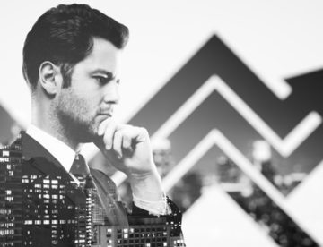 Thoughtful businessperson in suit on creative city background with chart arrows. Success concept. Double exposure. Black and white image