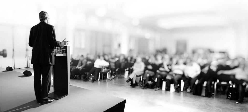 Redner steht vor Publikum - Vorträge sind wichtig für Kanzleimarketing