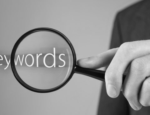 Man sucht mit Lupe das Wort Keywords - bildlich für Kanzleimarketing und Suchmaschinenoptimierung