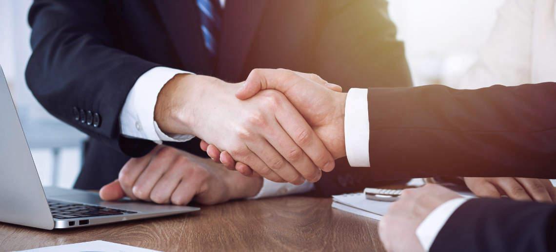 Vertragliche Einigung per Handschlag am Schreibtisch