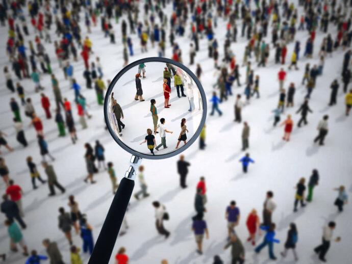 Modellfiguren mit Lupe - bildlich für SEO und Suche der Zielgruppe im Kanzleimarketing